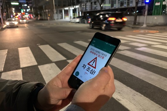 "Kim Jong-hoon, a senior researcher at Korea Institute of Civil Engineering and Building Technology (KICT) demonstrates an application 'Watch Out' that gives an alert to a user distracted by using smart phone while crossing a zebra crossing, in Ilsan, South Korea, March 12, 2019. Picture taken on March 12, 2019. The message reads: ""A car is approaching from the left, watch out for the car"". REUTERS/Minwoo Park"