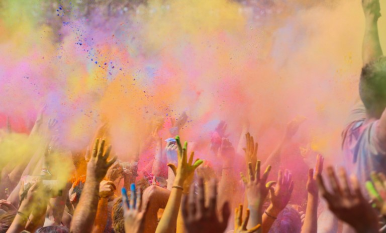 People enjoying the colorful Holi festival in Barcelona a indian tradition to welcome the spring covering himself of gulal powder, moment when all the crowd throwing the colorful powder to the air with arms raised. Catalonia, Europe.