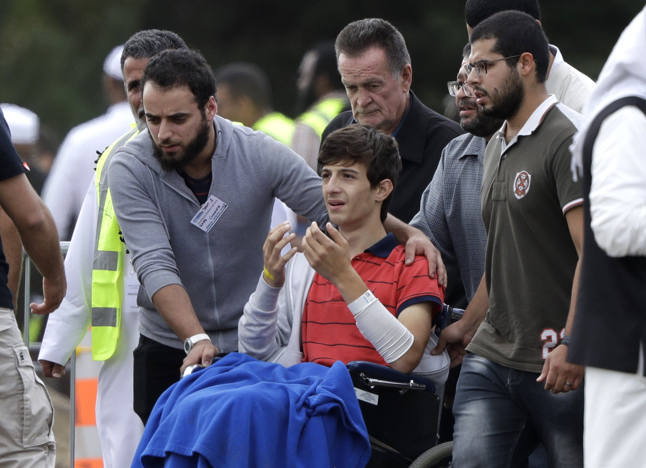 Zaed Mustafa, in wheelchair, brother of Hamza and son of Khalid Mustafa killed in the Friday March 15 mosque shootings reacts during their burial at the Memorial Park Cemetery in Christchurch, New Zealand, Wednesday, March 20, 2019. (AP Photo/Mark Baker)