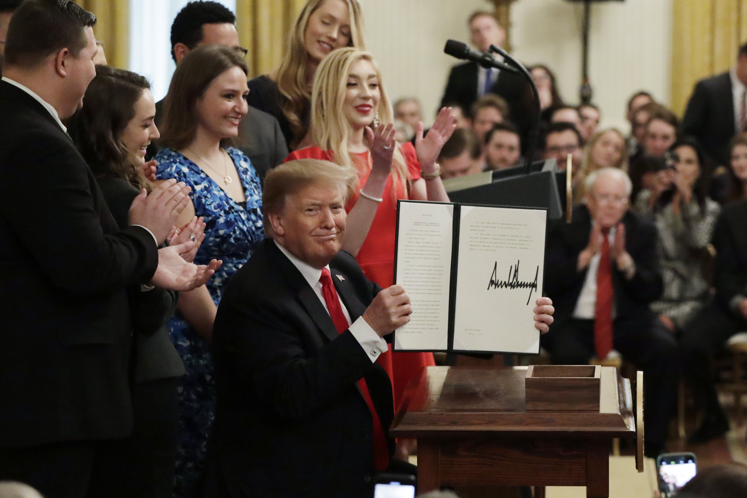 "President Donald Trump holds up an executive order on ""improving free inquiry, transparency, and accountability on campus"" after signing in the East Room of the White House, Thursday, March 21, 2019, in Washington. (AP Photo/Evan Vucci)"