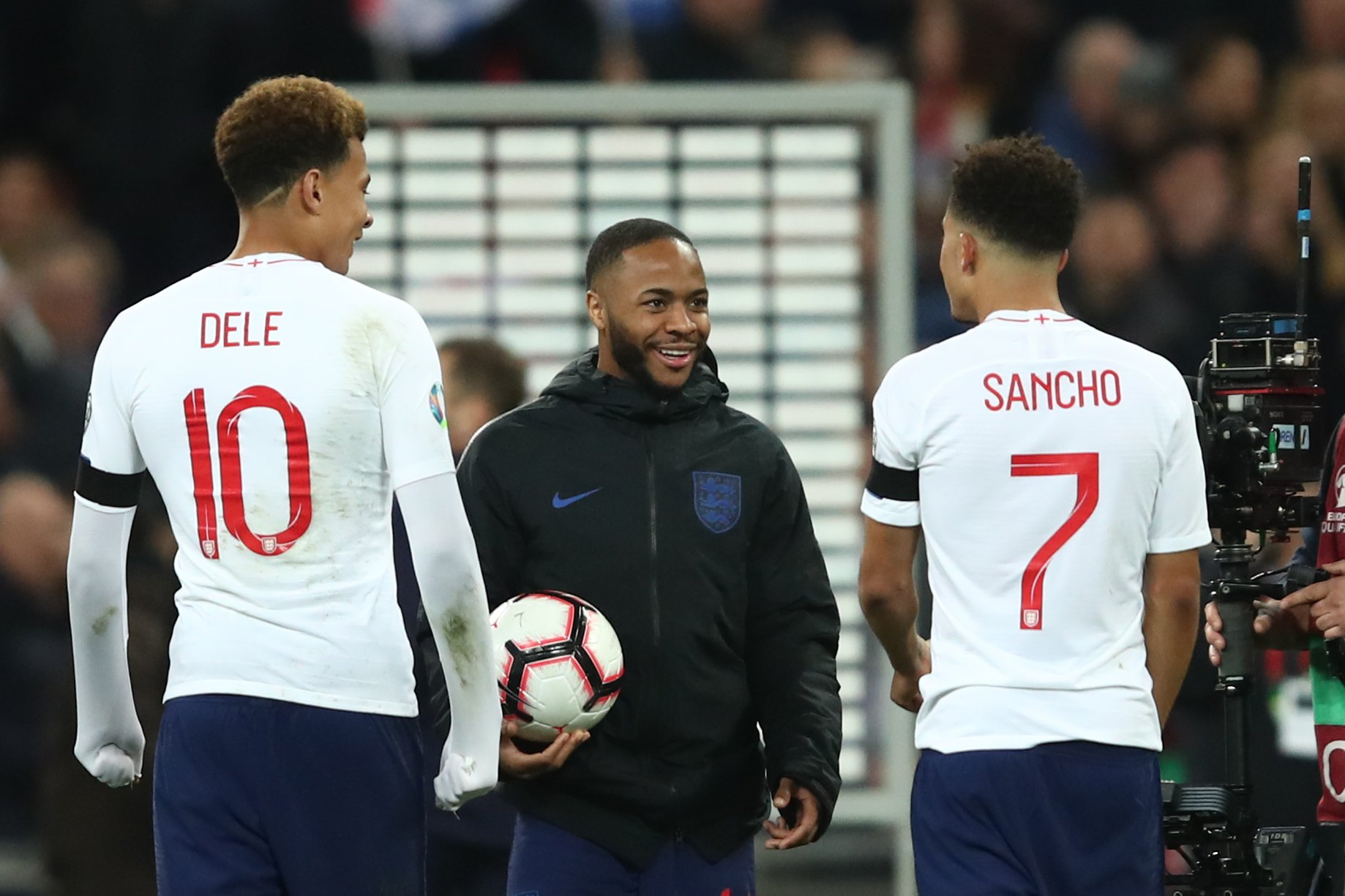 LONDON, ENGLAND - MARCH 22: Raheem Sterling of England walks off with the match ball as he speaks to Dele Alli and Jadon Sancho during the 2020 UEFA European Championships group A qualifying match between England and Czech Republic at Wembley Stadium on March 22, 2019 in London, United Kingdom. (Photo by Marc Atkins/Getty Images)