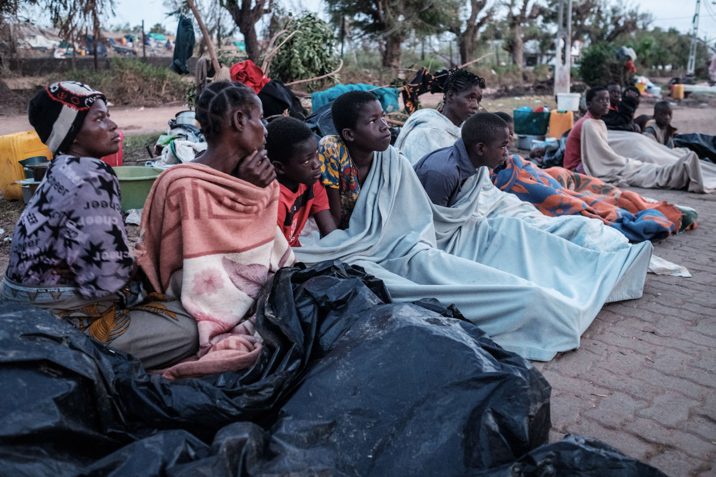 People who lost their home by the cyclone Idai wake up in the morning as they stay in shelter on a street in Buzi, Mozambique, on March 23, 2019. - The death toll in Mozambique on March 23, 2019 climbed to 417 after a cyclone pummelled swathes of the southern African country, flooding thousands of square kilometres, as the UN stepped up calls for more help for survivors. Cyclone Idai smashed into the coast of central Mozambique last week, unleashing hurricane-force winds and rains that flooded the hinterland and drenched eastern Zimbabwe leaving a trail of destruction. (Photo by Yasuyoshi CHIBA / AFP)YASUYOSHI CHIBA/AFP/Getty Images