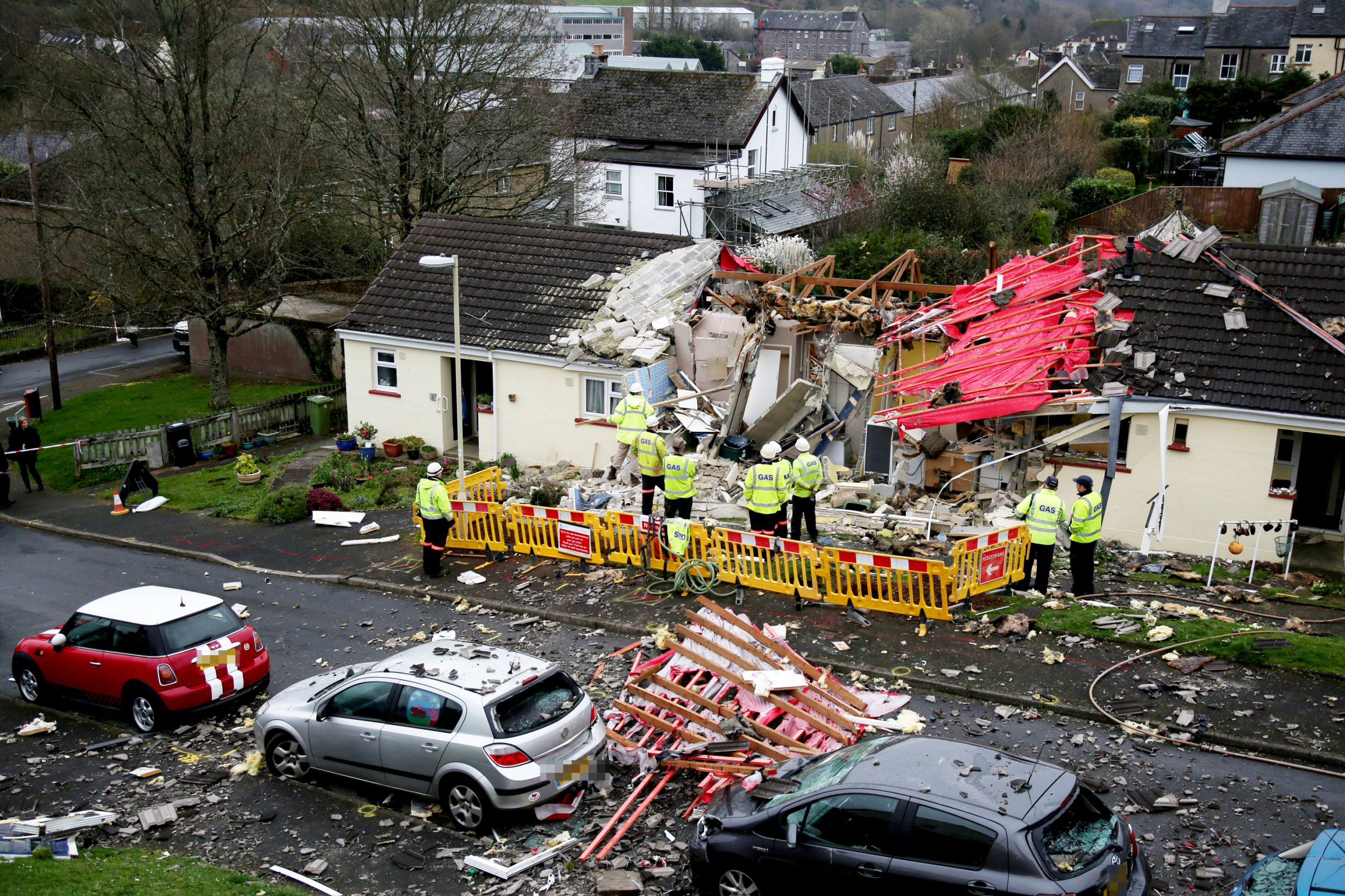 """Gas Explosion, Barn Park, Buckfastleigh. March 23, 2019. A pensioner had a miracle escape after a suspected gas explosion destroyed her bungalow - blowing off the walls and the roof. See SWNS story SWBRgas. Locals said the woman in her 70s walked out of the wreckage with the help of a young neighbour who heard the blast in Buckfastleigh, Devon, at around 8am this morning (Sat). Photos show the home was totally destroyed, with bricks and other debris littering the road. The woman is being treated in hospital for """"significant burns"""" while another person is being treated for minor injuries, police said. Neighbour Tom Hall, who lives 100ft from the blasted property in Barn Park, said the fact that the woman survived was a miracle."""