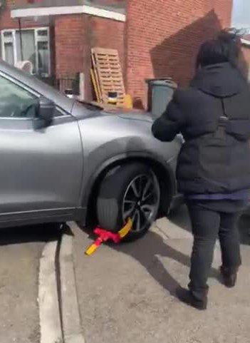 Grabs from Jam Press (Bailiff gets clamped) This is the moment a bailiff gets her car clamped while on the job for parking on a disabled mans drive. In the footage which was posted to social media you can see the bailiff on the photo to her office seeking advice after her car was clamped. The footage was posted to facebook by Kieren Dawson with the credit 'When baileifs say they gonna clamp u car and the g neighbour comes out and clamps theirs' and has been hailed as the best thing people have seen all day. ENDS