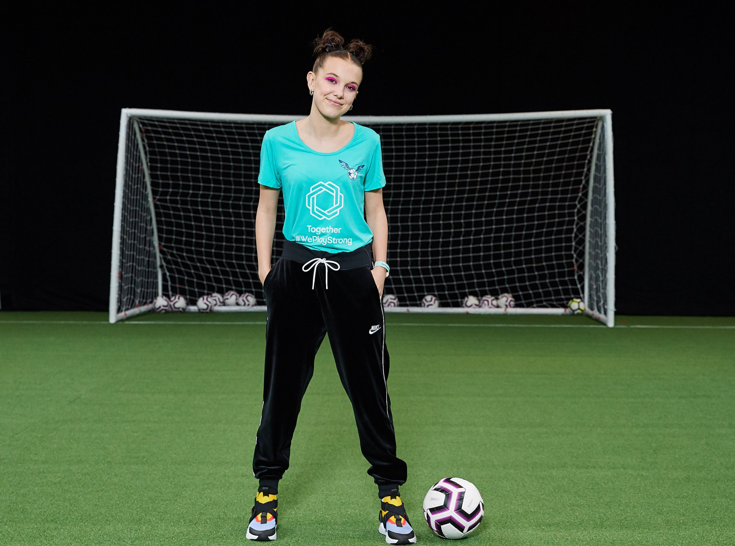 """Millie Bobby Brown shows off her football [soccer] skills - as she teams up with UEFA [Union of European Football Associations] to transform the game. The Stranger Things star has been unveiled as the newest ambassador of UEFA's Together #WePlayStrong campaign. The ground-breaking partnership is designed to transform the image of women s football and inspire young girls to play. Actress Millie, 15, is an avid Liverpool FC fan and grew up kicking a ball around with her football-loving family. She marked the collabortaion by surprising a group of young girls and joining in with a football skills session organised by UEFA at Wembley Stadium in London. She said: Kicking the ball around with the girls was really cool and fun. It felt great to be part of a team that has such a strong sense of unity."""" Through the Together #WePlayStrong campaign, UEFA aims to make football more culturally relevant and aspirational for girls in their teenage years, where they traditionally drop out in large numbers. Nadine Kessler, UEFA s Head of Women s Football, said: Millie Bobby Brown is a source of inspiration and motivation to so many young people across the world and we re excited to have her on board."""" Editorial use only. Must credit Courtesy of UEFA/MEGA. 26 Mar 2019 Pictured: Millie Bobby Brown for UEFA. Photo credit: Courtesy of UEFA/MEGA TheMegaAgency.com +1 888 505 6342"""