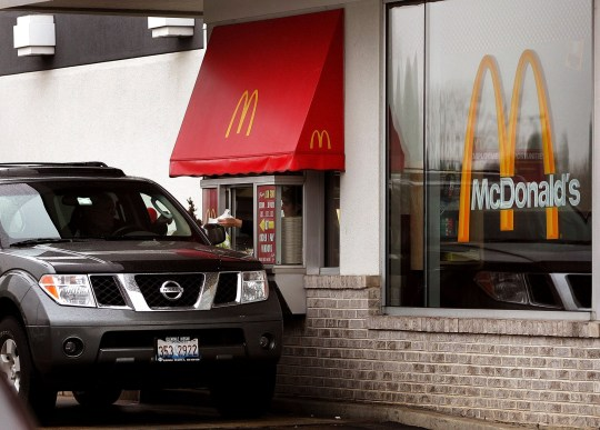 ROSEMONT, IL - JANUARY 17: A customer picks up their order at a McDonald's drive-thru window January 17, 2006 in Rosemont, Illinois. McDonald's, reportedly in an effort to satisfy consumers in a hurry for food-to-go and traffic related to such, has built dual drive-ups at some of their restaurants. Also, McDonald's today reported global comparable sales for December were up 5.0 percent. (Photo by Tim Boyle/Getty Images)