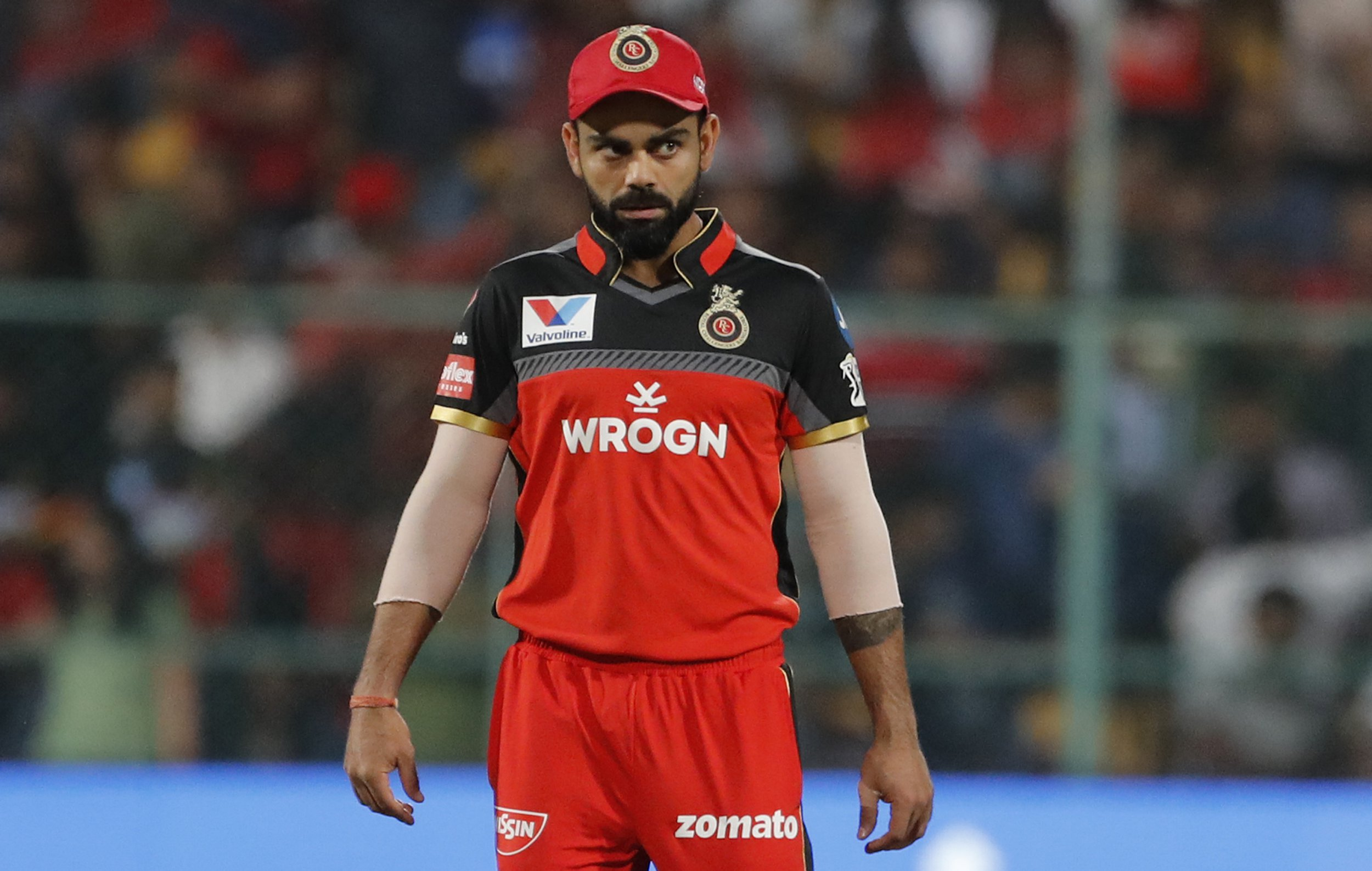 Royal Challengers Bangalore captain Virat Kohli walks into the field at the start of the VIVO IPL T20 cricket match between Royal Challengers Bangalore and Mumbai Indians in Bangalore, India, Thursday, March 28, 2019. (AP Photo/Aijaz Rahi)