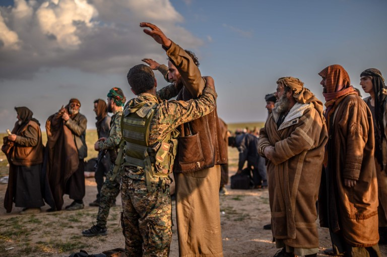 Men suspected of being Islamic State (IS) fighetrs are searched by members of the Kurdish-led Syrian Democratic Forces (SDF) after leaving the IS group's last holdout of Baghouz in Syria's northern Deir Ezzor province on February 22, 2019. (Photo by Bulent KILIC / AFP)BULENT KILIC/AFP/Getty Images