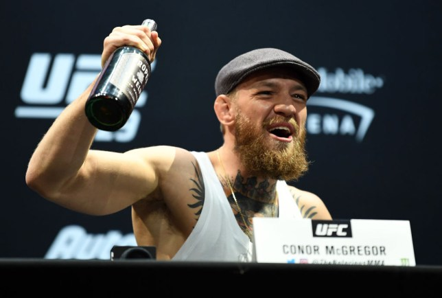 Conor McGregor holds up a bottle of his whiskey