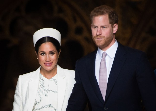Meghan Markle in a white dress, jacket and hat and Prince Harry wearing a suit with a pink tie