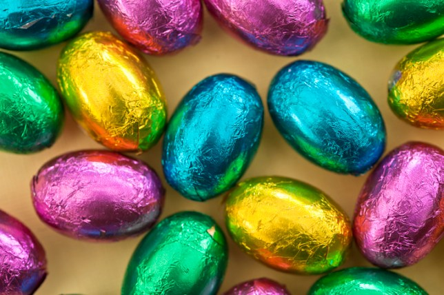Close-up of colourful foil-wrapped Easter eggs on a yellow background