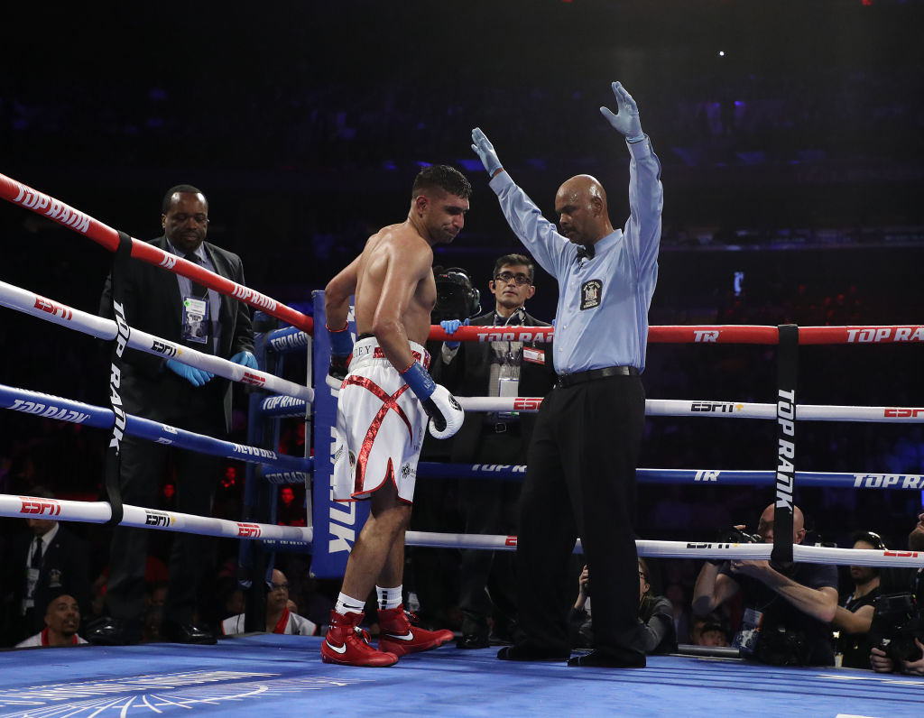 Amir Khan reacts as the referee stops the fight