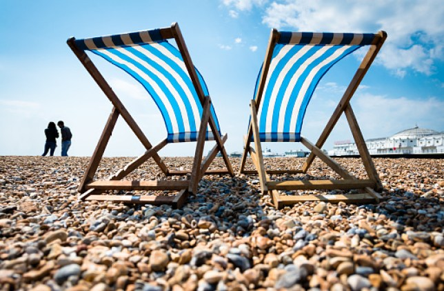 Silhouette of young couple and two empty deck chairs on the beach at Brighton with the Palace Pier in the distance