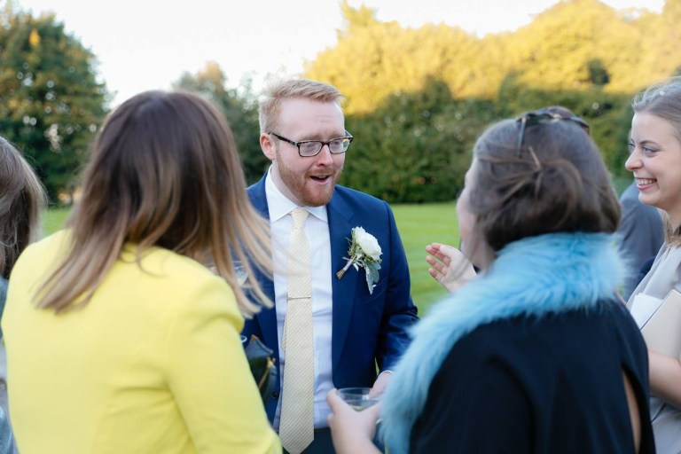 A man who got divorced before he was 30 smiles at guests on his wedding day