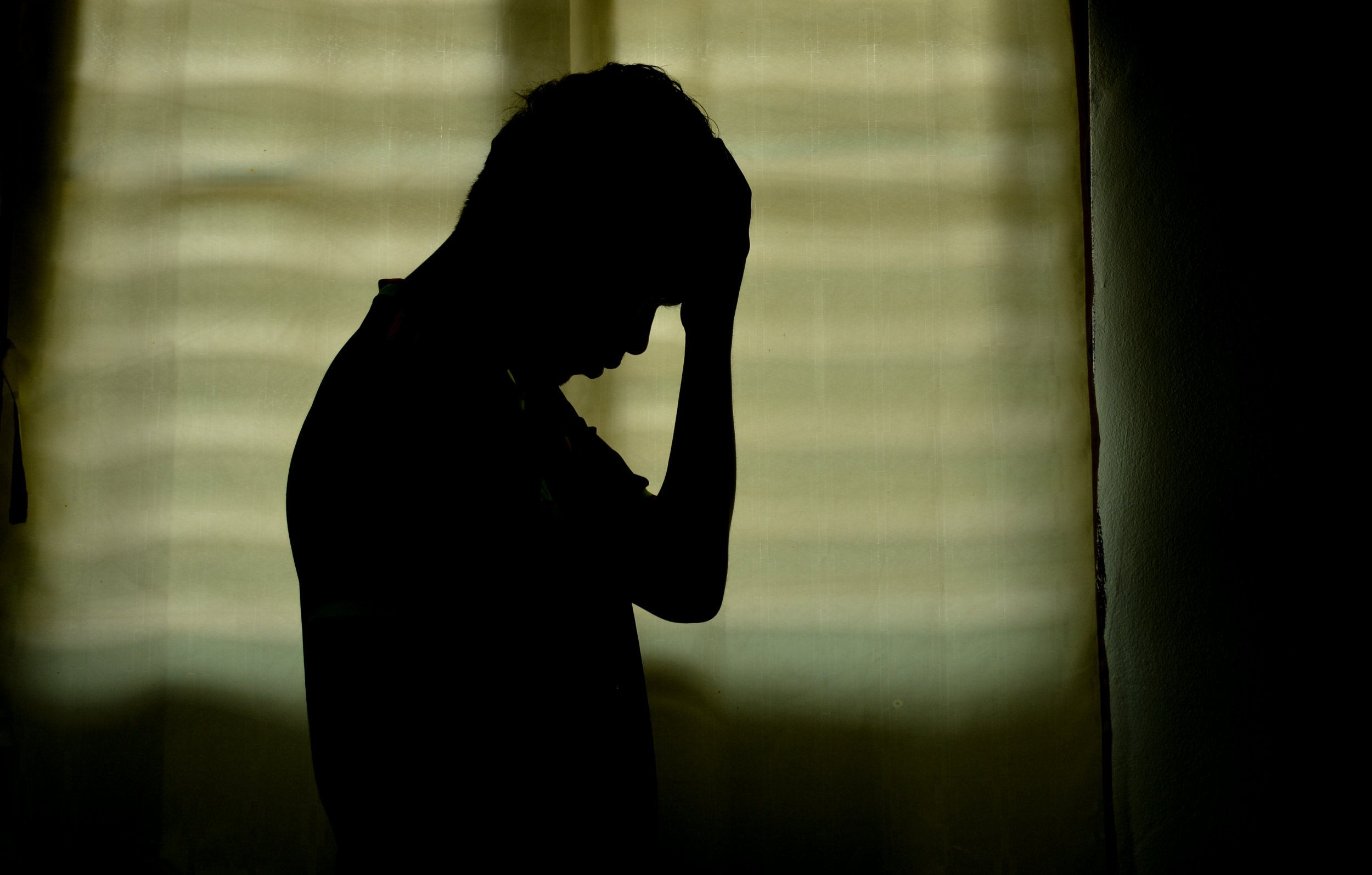 Man silhouette disappointed Window background with light in the room.; Shutterstock ID 677984281; Purchase Order: -