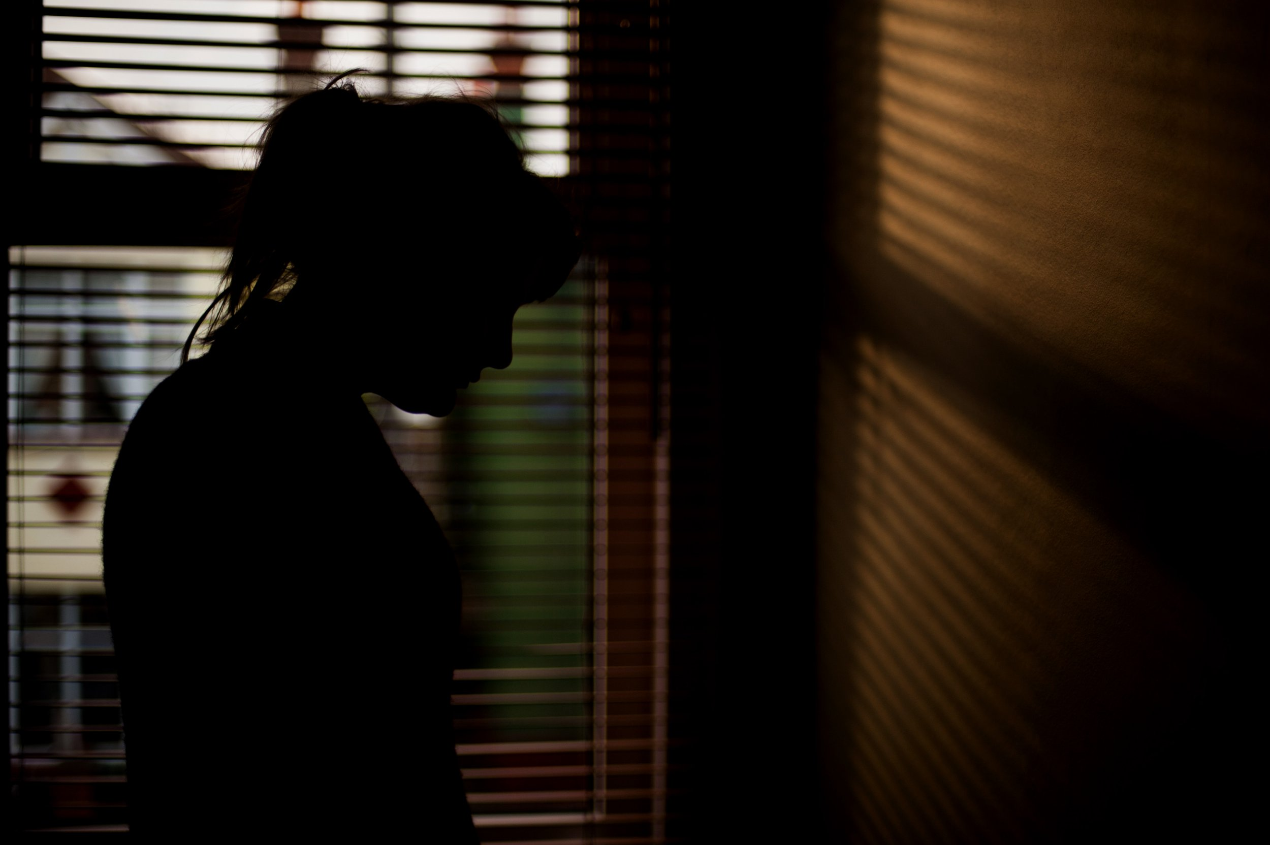 The silhouette of a woman standing by a window. IT is late in the day and the light is streaming through the blinds in front of the window, creating a striped pattern on the wall. The woman is standing in profile with her hair tied back in a ponytail.