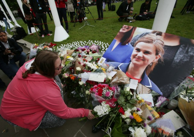A woman leaves flowers in Parliament Square, London, after Labour MP Jo Cox was shot and stabbed to death in the street outside her constituency advice surgery in Birstall, West Yorkshire.