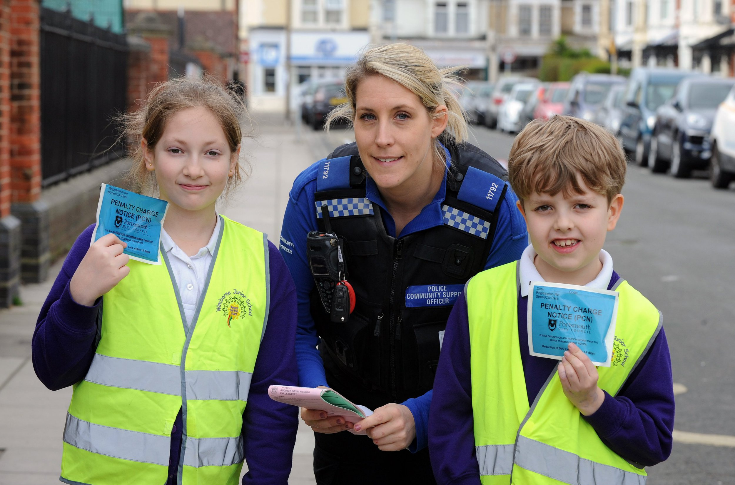 Pictured: PCSO Susan Smith with (left) Hannah-Elissa Badnell (10) and Josh Ost (8). Council chiefs in one of the UK's worst-polluted cities are considering banning cars from school roads in a bid to improve air quality. Environmentalists in Portsmouth, Hants, are in talks with councillors and have urged them to shut school roads to traffic during drop-off and pick-up times. The city has come under fire for its worrying pollution levels and currently faces having a Clean Air Zone imposed, which could force drivers to pay up to ?8 a day to use their cars. The latest readings of dangerous nitrous dioxide (NO2) in Portsmouth show that 16 areas in the city are above the 'safe' level - up from four in 2017. SEE OUR COPY FOR DETAILS. ? Portsmouth News/Solent News & Photo Agency UK +44 (0) 2380 458800