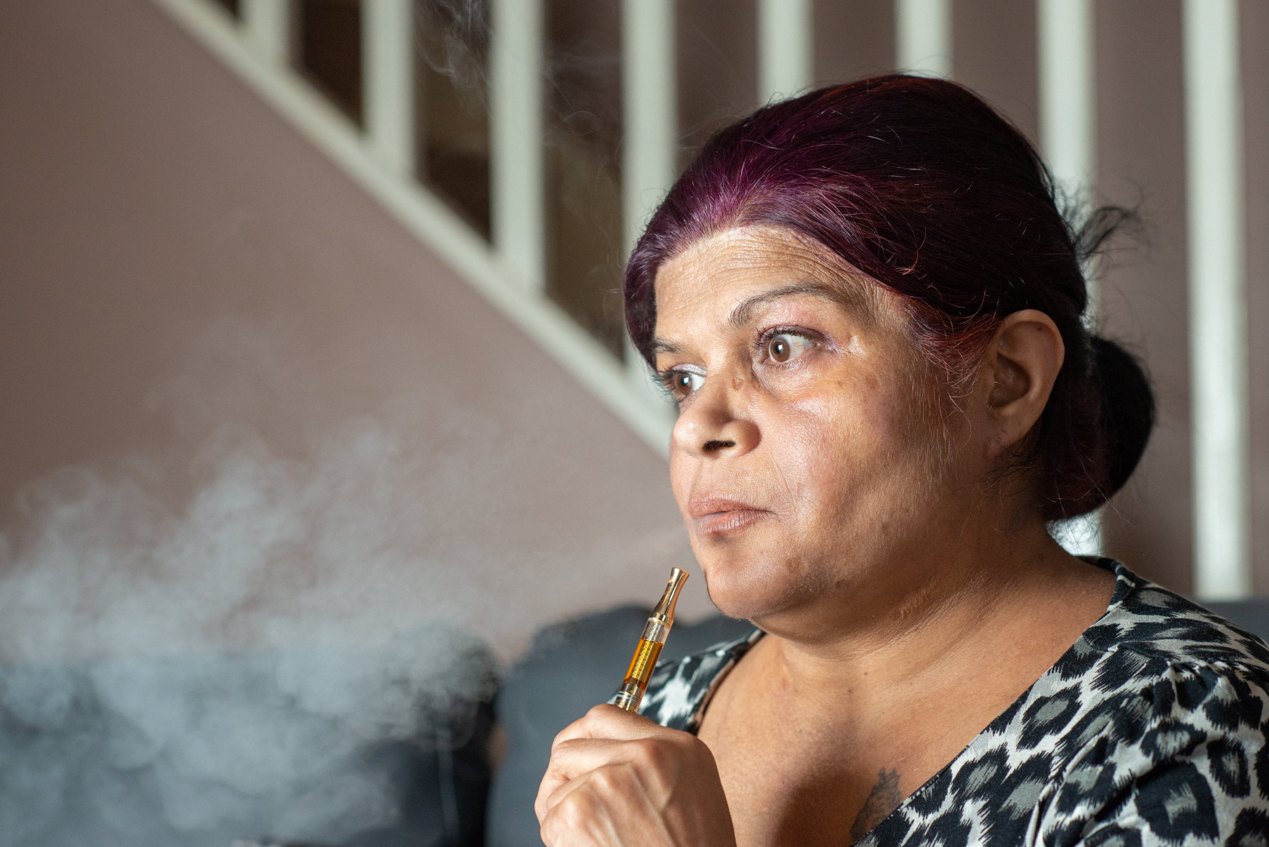 Sue Dhillon smoking from a vape that contains cannabis oil. See SWNS copy SWTPdrug: A mum who was given weeks to live after she shunned chemotherapy has baffled doctors by treating her cancer -- with illegal super strength cannabis and Manuka honey. Susan Dhillon, 51, a mum-of-three, was diagnosed with inoperable stage four cancer of the mouth, nose and lower skull in June 2018. Doctors said unless she had chemotherapy - and then incredibly risky facial surgery - her only option was end of life care.