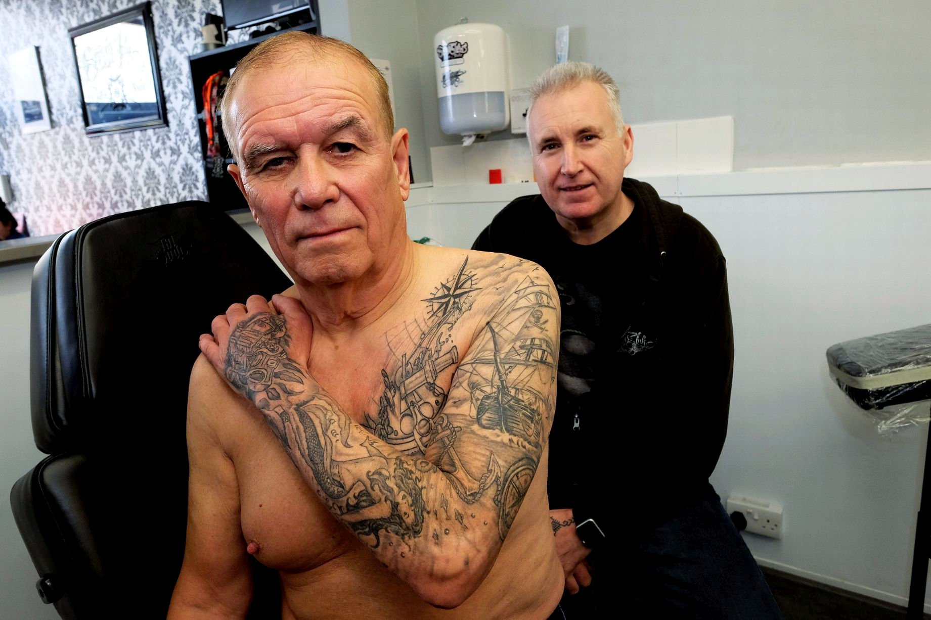 Grandad, Robert Luff, 73, who says he has not given a second thought to the occasional funny look since he discovered a passion for tattoos a year ago - Pictured with tattooist Mark Pennell. See SWNS story SWBRink. Robert, who has lived in Sea Mills, Bristol, his whole life, came to the world of body art late, but he is making up for lost time now. After his wife Marilyn bought him a voucher for Shirehampton?s Serious Ink Tattoo Studio for Christmas in 2017, it took him a few months to pluck up the courage for a visit. But he has fallen in love with tattoos and gradually built up a full sleeve on his left arm, spreading onto the left half of his chest. Robert, who built and repaired ships at Bristol Harbour for more than 15 years, says the ink is partly a way of honouring his former workmates, many of whom have passed away. All of the tattoos are connected to the sea. A grand ship is the centrepiece, on his upper arm, surrounded by a treasure chest, cannon, mermaid and other maritime art.