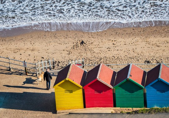 A man walks a dog near colourful beach huts on Whitby beach in Yorkshire. PRESS ASSOCIATION Photo. Picture date: Friday April 12, 2019. See PA story WEATHER Spring. Photo credit should read: Danny Lawson/PA Wire