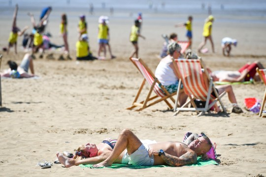People sunbathe on the beach at Weston-super-Mare, Somerset, as hot weather continues across the UK.