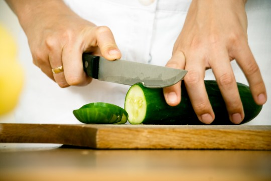 Females hands cutting cucumber on kitchen desk