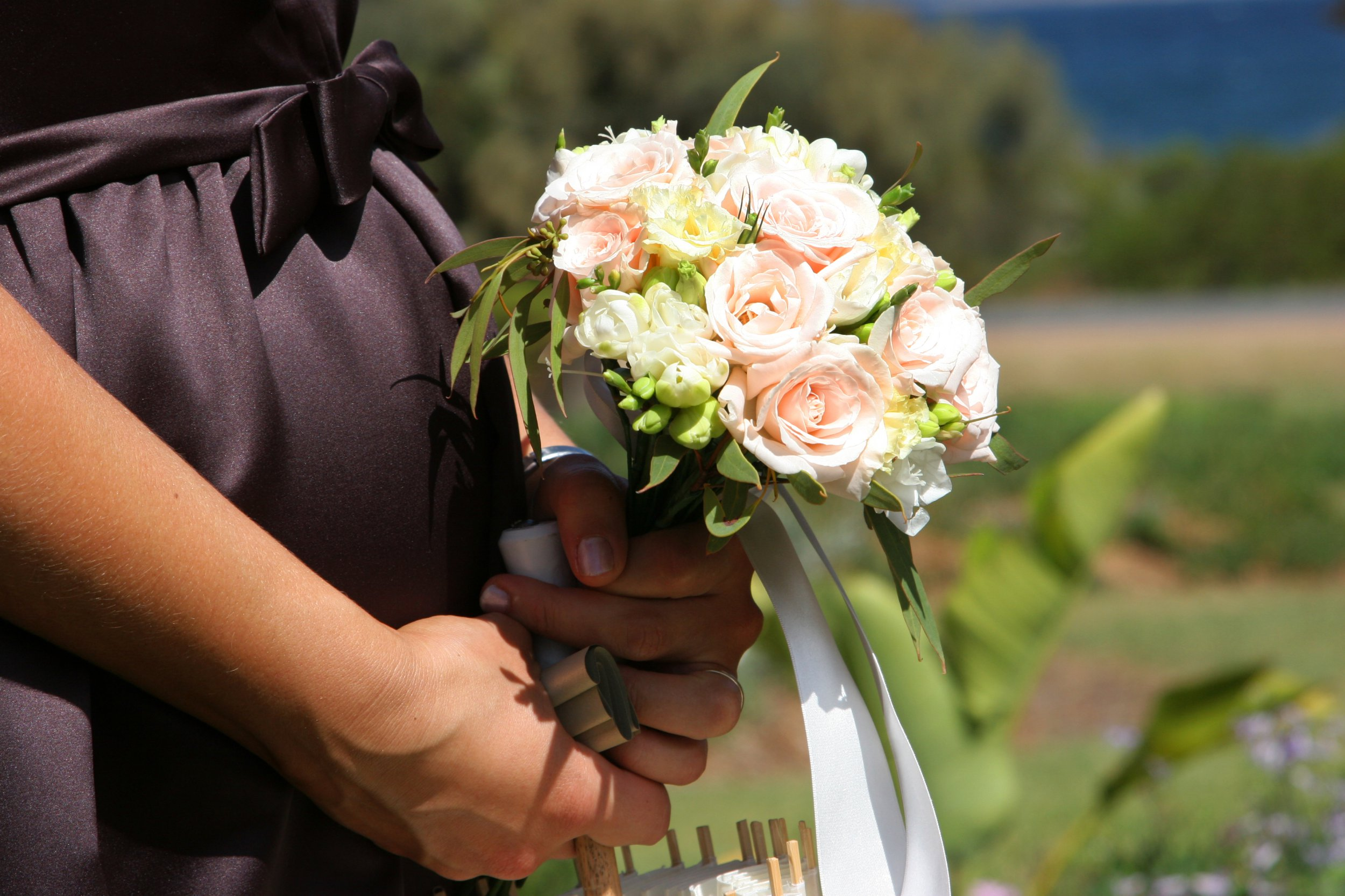 A bridesmaid with her flowers and parasol