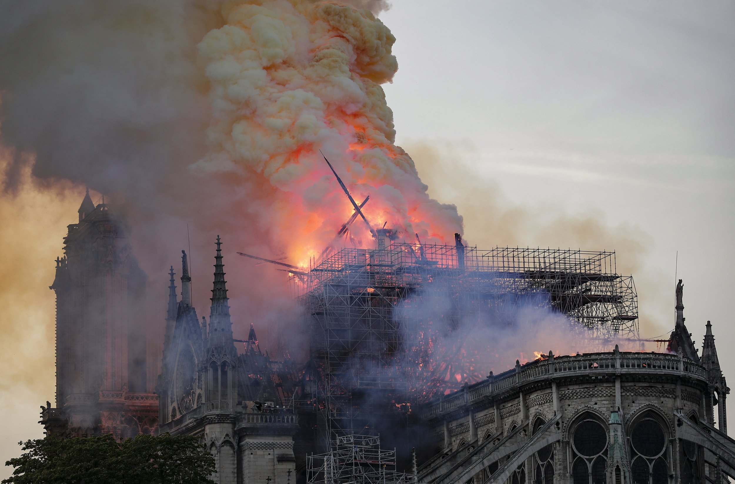 epa07509101 The spire collapses while flames are burning the roof of the Notre-Dame Cathedral in Paris, France, 15 April 2019. A fire started in the late afternoon in one of the most visited monuments of the French capital. EPA/IAN LANGSDON