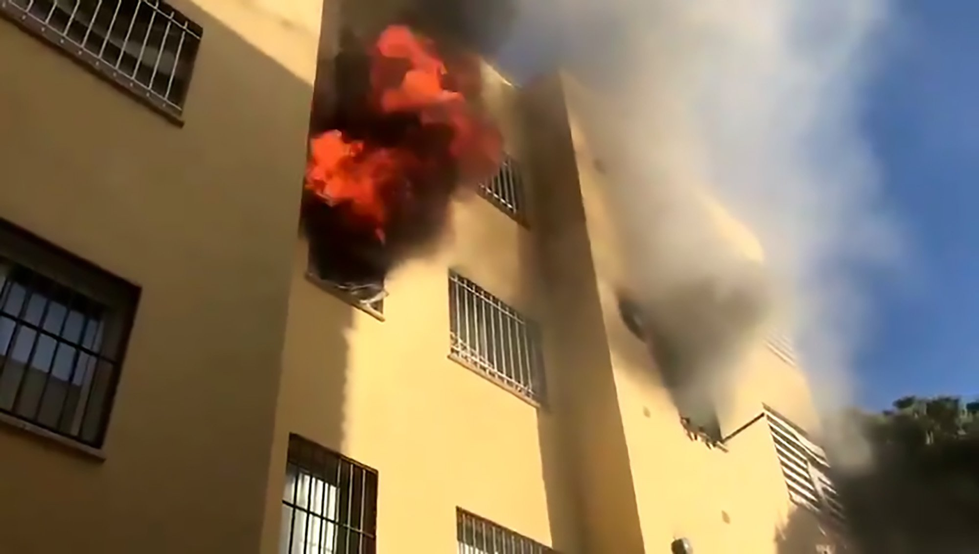 Pic Shows: The building on fire; SPAIN: This is the moment a brave resident climbs up the front of a building as a fire rages inside to help a woman in shock on a top-floor balcony.
