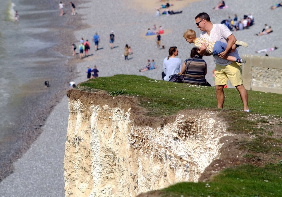 ? Licensed to London News Pictures. 22/04/2019. Birling Gap, UK. Reckless members of the public risk their lives on the edge of the crumbling chalk cliffs of the Seven Sisters near Eastbourne, UK. The iconic sheer white cliffs are up to 400 feet high and have had recent record cliff falls due to erosion, but many people, some even holding children, cannot resist the temptation to peer over the edge to get photos. Some people are even seen jumping in the air just feet from the edge. Photo credit: Peter Cripps/LNP
