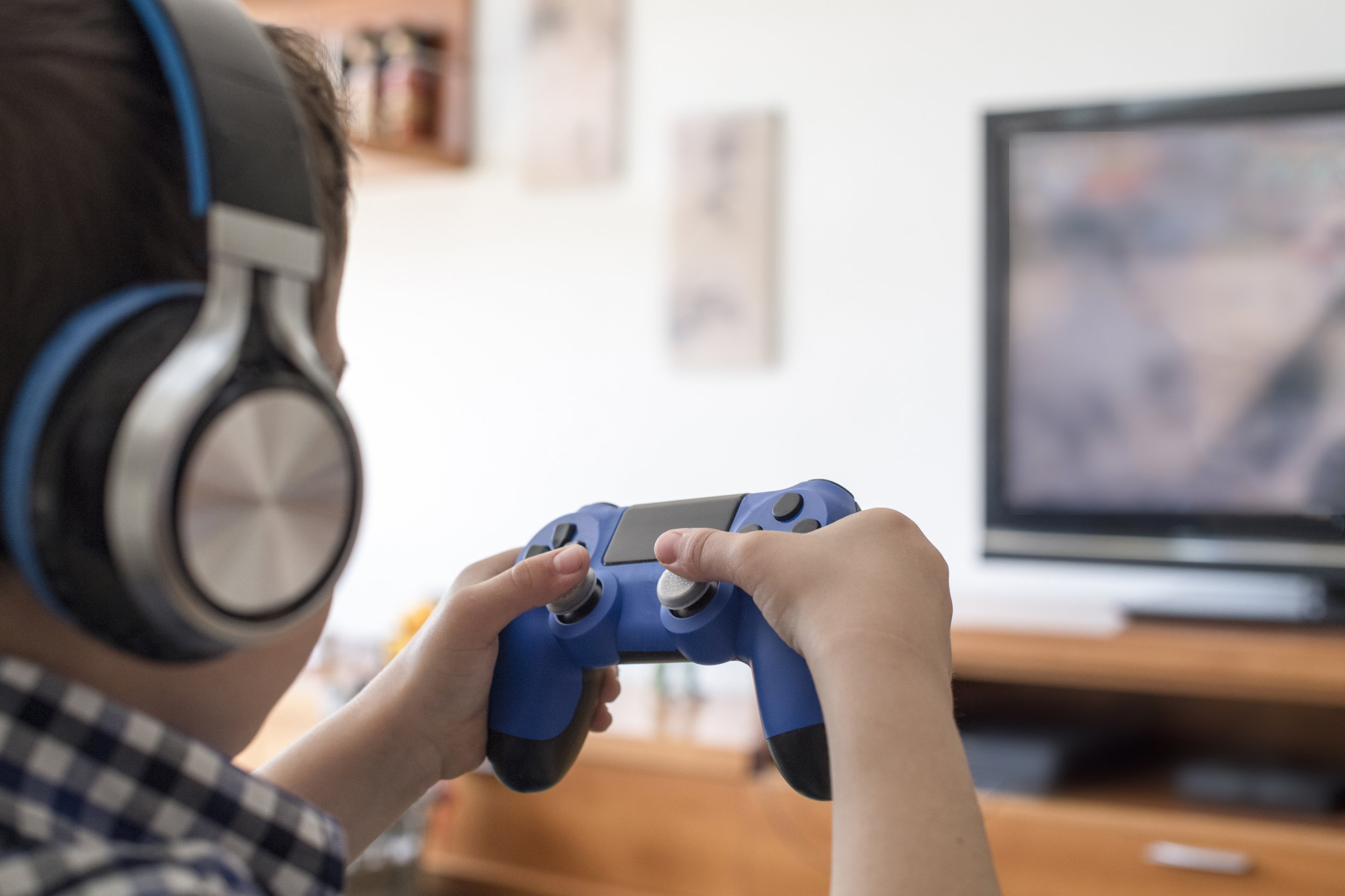 Boy Playing on console with videogames joystick at home