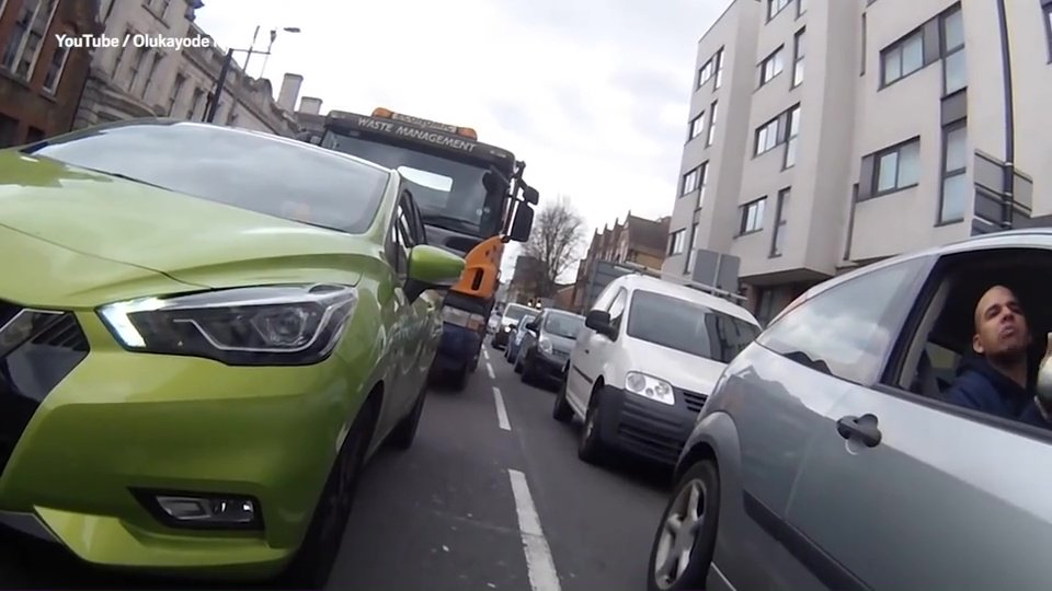 A cyclist is knocked off his bicycle when an enraged driver hits out at him for cycling between queuing cars. The driver of a silver Ford Focus shouts out to the cyclist to 'keep to the side of the road' during the altercation at a set of traffic lights in Greenwich. He says: 'Keep to the side of the road, you're not a car.' https://videos.metro.co.uk/video/met/2019/04/24/1724477231626078161/960x540_MP4_1724477231626078161.mp4