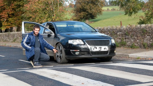 """Chris Fitzgibbon with his lowered suspension car at one of the speed bumps near his house which is preventing him from driving into his village. See SWNS story SWOCbump; A young driver who lowered the suspension on his modified car is now unable to drive into his home village - after speed bumps were installed on every entry road. Christopher Fitzgibbon, 23, dropped the height of his VW Passat to just four inches off the ground to improve the stability and """"look fresh"""". But he is gutted after council chiefs installed six-inch high speed bumps on the only three entry roads into his local community. He now has to drive an additional 600 miles every month to get to work and has suffered ??2,000 worth of damage trying to scrape over the traffic calming measures."""