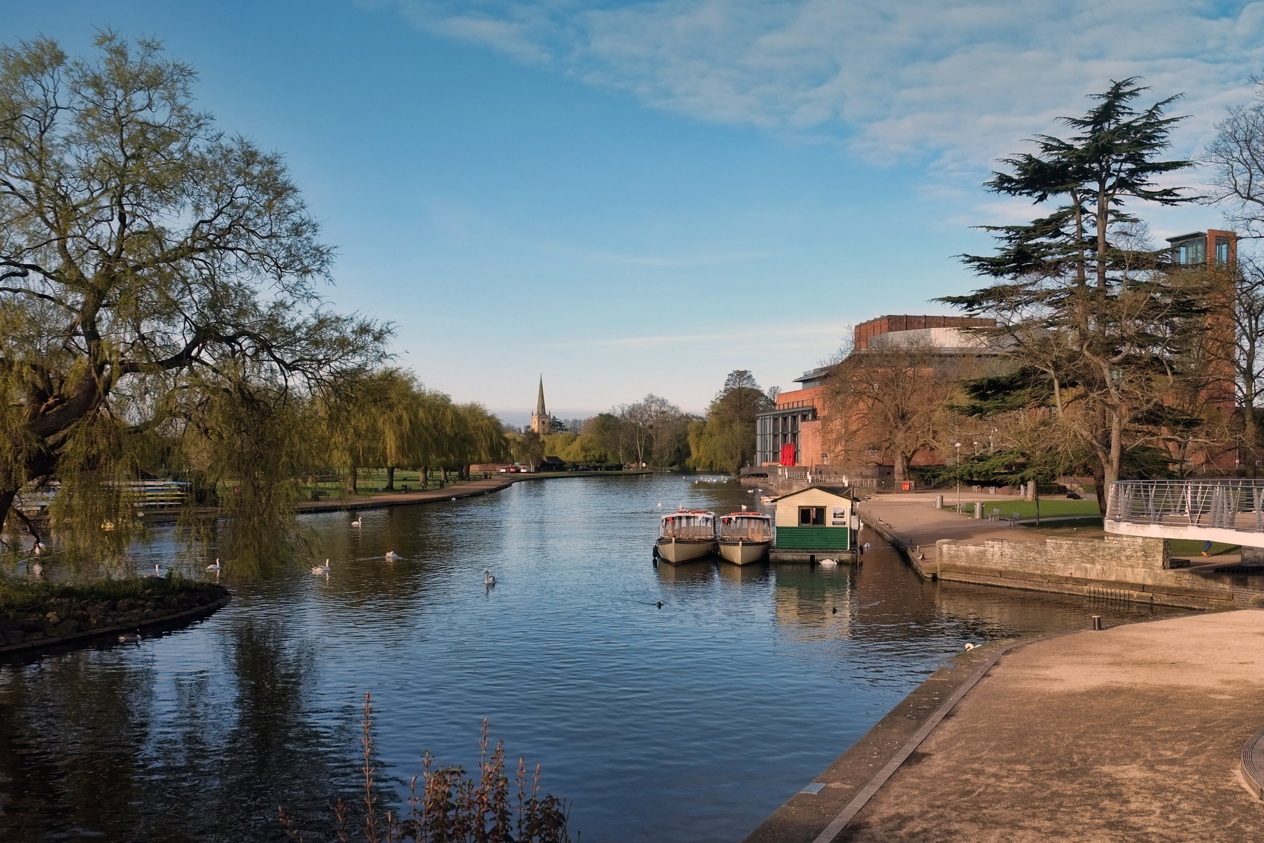 General perspective of a River Avon during Stratford-upon-Avon, with a Royal Shakespeare Theatre and a Holy Trinity Church in a background.