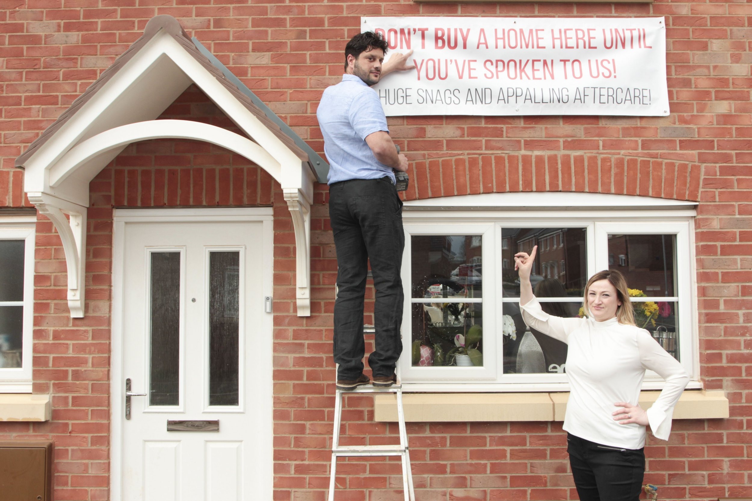 Pic By Dilantha Dissanayake/ Caters News - (PICTURED: Faye, 40 and Neil Douglas, 38 in Droitwich point at buyers warning sign of badly built house. Pic Taken: 25/04/2019) - A pair of disgruntled homeowners are so fed-up with their home from hell they hung a giant sign from the front of their new build to warn off other buyers. Mum-of-two Faye Douglas, 40, and hubby Neil, 38, paid 286,000 for the four-bedroom home on the Persimmon development in Droitwich, Worcs after the birth of their twin boys as a forever home. But Faye claims that their lives have become a living nightmare after the house was allegedly left strewn with third-rate building work including wonky walls and doors and windows that dont open properly.SEE CATERS COPY