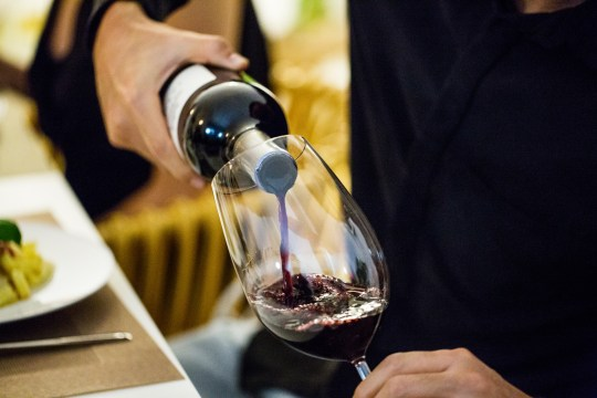 A stock image of a man pouring a bottle of wine