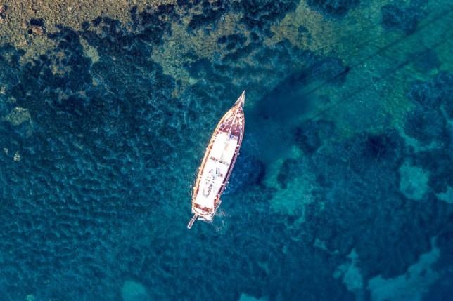 A yacht sailing in the sea around Milos Island, Greece