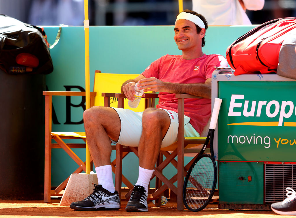 Federer smiling at the side of a clay court in Madrid