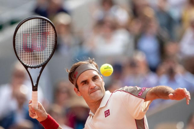Roger Federer hits a ball into the French Open crowd after his latest win