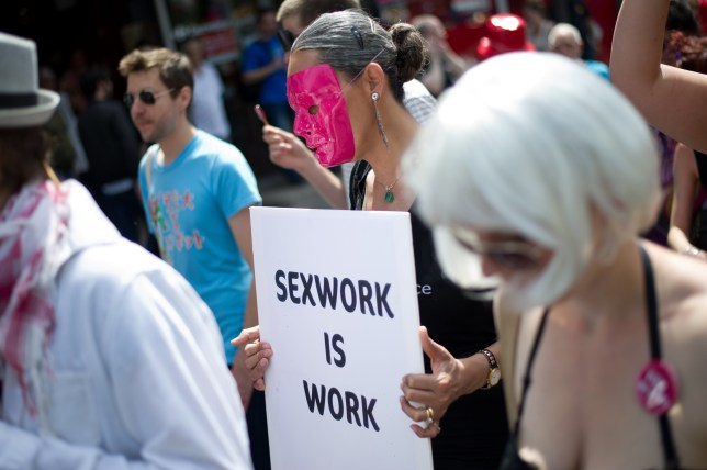 Sex workers protest for their rights, with one holding up a sign that says 'Sexwork is work'