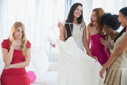 A bride and her bridesmaids looking at dresses
