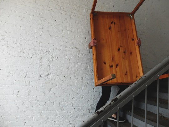 A man carrying a table down some stairs