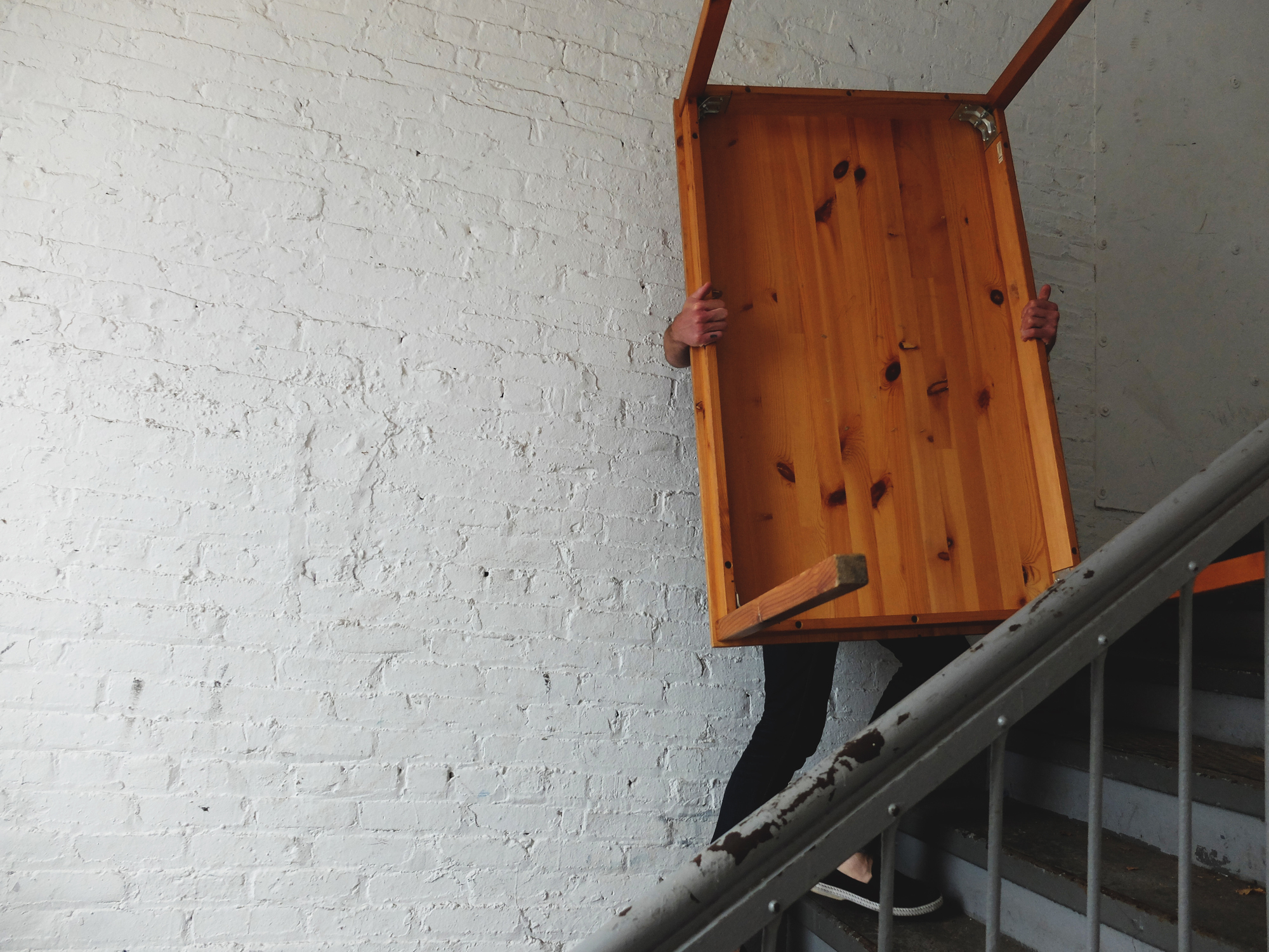 A male carrying a list down some stairs