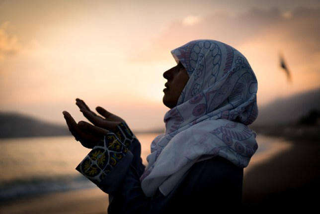 Muslim woman praying with hands up at sunset on beach