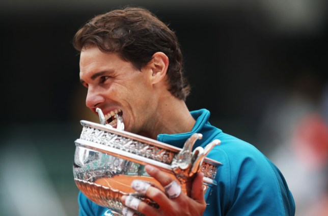 Rafael Nadal bites the French Open trophy after winning the title