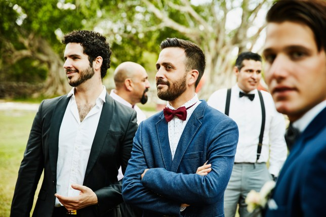 Male friends hanging out together during outdoor wedding reception