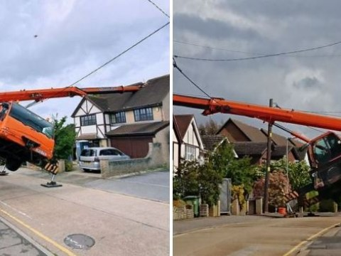 Huge orange crane falls over and crashes on to house trapping driver