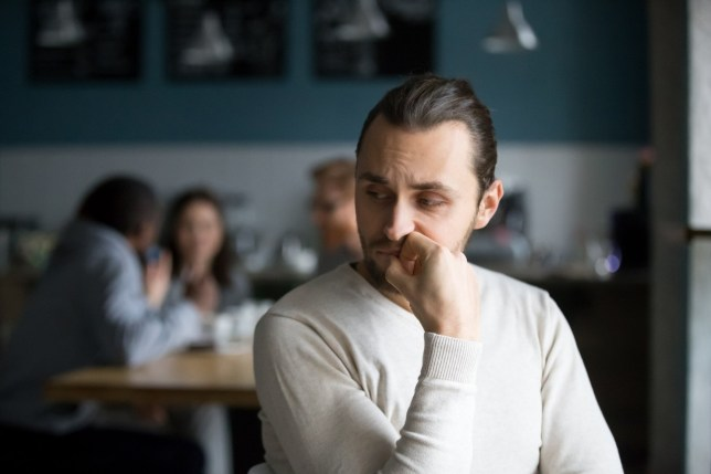 Upset millennial outsider feel offended lack company, young outcast guy suffer from discrimination, jealous of friends hang out together in caf????, envious male loner depressed sit alone in coffeeshop