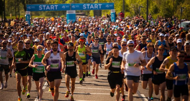 Runners taking part in the Milton Keynes Marathon with the starting line behind them